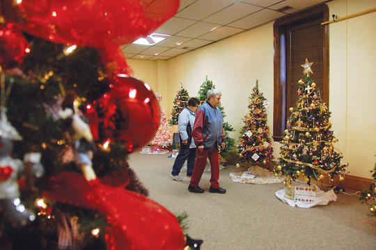 Donna Rymer, left, and Mary Ann Nikolas wander among the bevy of decorated Christmas trees at the Dacotah Prairie Museum. Watch a video of the Christmas exhibit at AberdeenNews.com. American News Photo by Calvin Men
