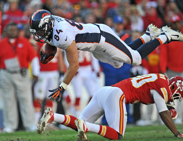 Tight end Jacob Tamme #84 of the Denver Broncos goes airborne after getting upended by defensive back Jalil Brown #30 of the Kansas City Chiefs during the second half on November 25, 2012 at Arrowhead Stadium in Kansas City, Missouri. Denver defeated Kansas City 17–9.