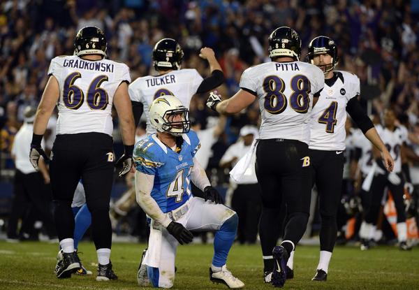 Kicker Justin Tucker #9 of Baltimore Ravens celebrates hitting the game-winning field goal as Corey Lynch #41 of the San Diego Chargers looks on during the Raven's overtime for a 16–13 win over the San Diego Chargers on November 25, 2012 at Qualcomm Stadium in San Diego, California.