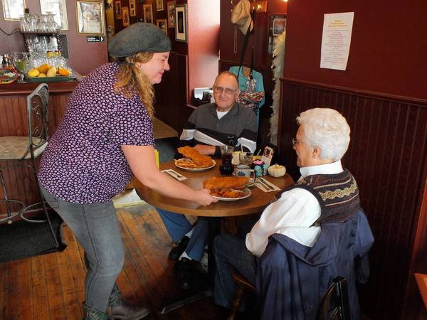 Jeri Halperin delivers two of her husband's award-winning pork tenderloin sandwiches to diners Bill and Leila Henkle.