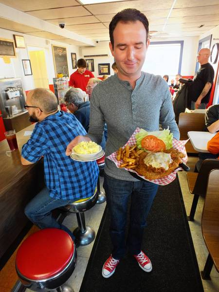 Owner Brad Magg serves up one of his famous pork tenderloin sandwiches, along with sides of beer-battered French fries and homemade potato salad.