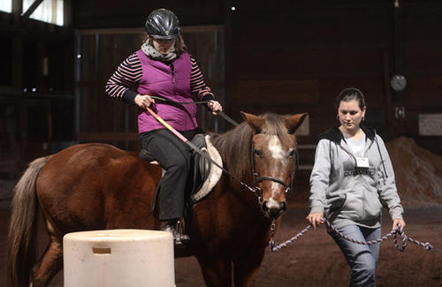 Christine DeHaven, 12, of Bushkill Township, takes her horseback riding lesson on Snickers, at Equi-librium in Snydersville on Wednesday.  Christine is an 8th grader at Nazareth Middle School and is autistic. Assisting her with Snickers is Heidi Weller, 23 of Bartonsville.