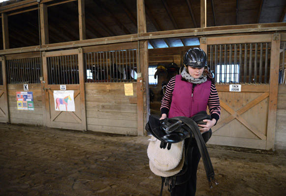 Christine DeHaven, 12, of Bushkill Township, carries the saddle she is going to use during her horseback riding lesson from the tack room to her horse, Snickers, at Equi-librium in Snydersville on Wednesday. Christine is an 8th grader at Nazareth Middle School and is autistic. Equi-librium equine-assisted therapy that uses horseback riding as a tool to help people with special needs to regain their physical balance.