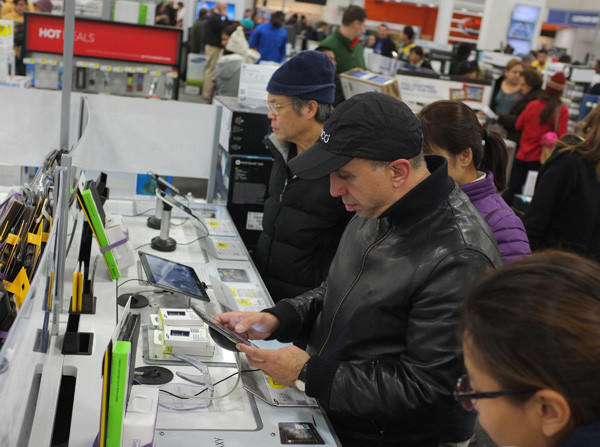 Shoppers look at tablet computers (perhaps in preparation for Cyber Monday) at a Best Buy in Rockville, Md.
