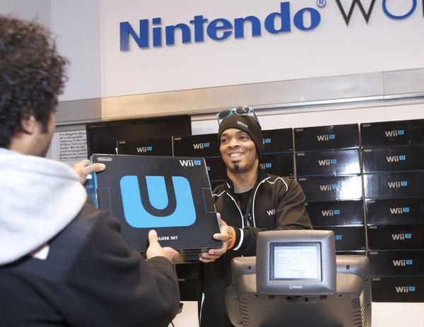 A fan buys one of the first Wii U systems at a midnight launch event in New York City.
