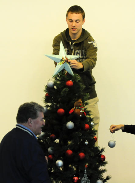 Newington High School seniors and teachers decorate their Christmas tree in Avery Hall at the Wadsworth Atheneum on Monday morning. From left is teacher Dennis Person and at top is senior Bryan Gionfrideo, 17. The museum is hosting its 39th Festival of Trees and Traditions from Nov. 30 through Dec. 9.