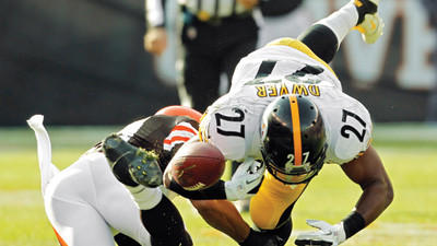 Pittsburgh Steelers running back Jonathan Dwyer fumbles on a hit by Cleveland Browns safety T.J. Ward in the second quarter of Sunday¿s game in Cleveland.