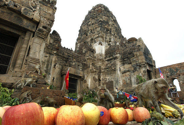 Monkeys dine on fruit at Prang Sam Yot. The Khmer-style temple dates to the 13th century. Before being converted to a Buddhist temple, it was a Hindu place of worship.
