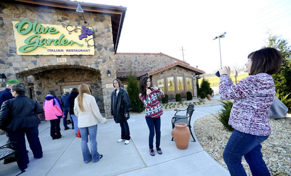 While waiting in line for the opening of Olive Garden in Martinsburg, W.Va., Monday morning, Yvette Mason, right, takes a photo of her daughter, Hannah Mason, with a thumbs up in front of the restaurant on Foxcroft Avenue. The restaurant is Hannah's favorite, and the two planned to attend the opening of the restaurant on the day she was getting her braces off.