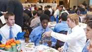 Corona del Mar's Cayman Carter, left, Kai Wilson, and Tim Reinhardt right, look through a magazine during the CIF football luncheon at The Grand in Long Beach on Monday.