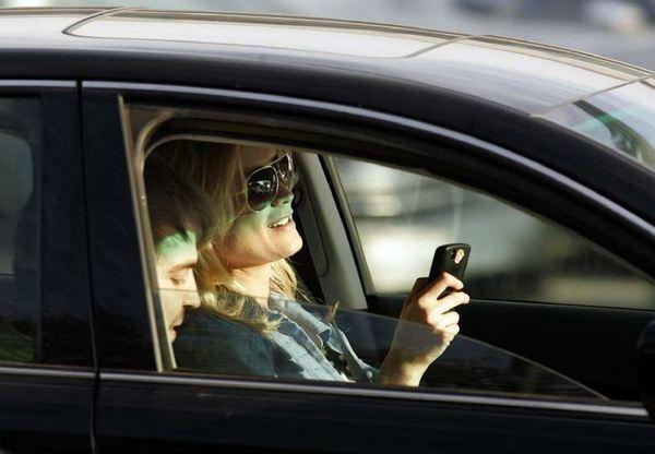 A motorist looks at her phone while behind the wheel in this 2010 photo.