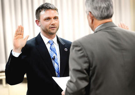 Hagerstown Mayor David S. Gysberts left is sworn in Monday night by Clerk of Circuit Court Dennis Weaver, right, in the council chambers in downtown Hagerstown.