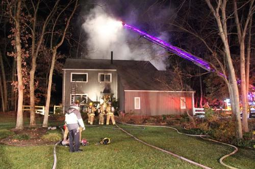 A view from the front of the house as responders from Howard County's Department of Fire and Rescue services battle the blaze in the back.