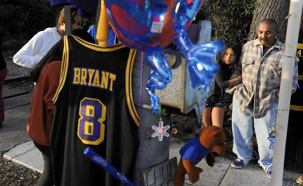 "Angel Baldenegro, right, holds his daughter Melissa, 10, at the site of a memorial where his friend Phillip Moreno was hit by a motorist along Torrance Boulevard in Torrance on Saturday night. Bud Light beer bottles, a miniature Dodgers bat, a Kobe Bryant jersey, balloons and flowers lay at the memorial along with notes with Moreno's nickname, ""Chud."""
