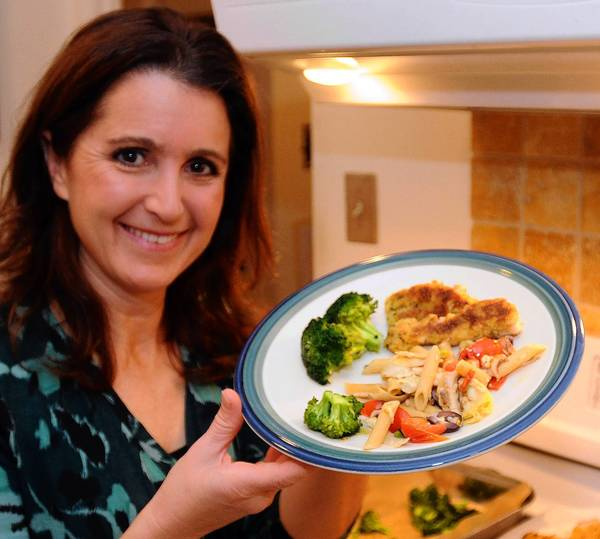 "Health writer Alisa Bowman holds a plate with Catfish fingers with spicy mayonaise and Penne pasta with mushrooms and artichokes and a side of broccoli in her kitchen on Sunday. Alisa has found innovative ways to boost your Vitamin D intake and improve your health. She describes her strategy in her new book, "" The 7 Day Slim Down."""
