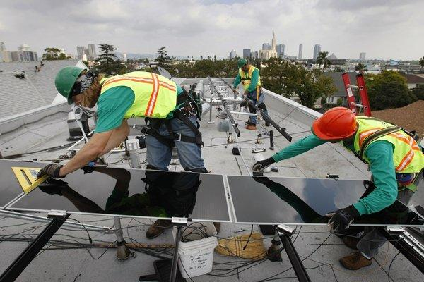 SolarCity installers work on a Los Angeles property. The company said it expects its shares to price at $13 to $15 apiece in its initial public offering.