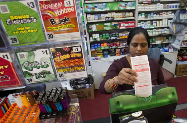 Jyoti Patel processes a Powerball play slip at RaceWay on Mercury Boulevard on Tuesday afternoon.
