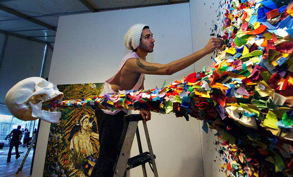 "Anthony Spinello, of Spinello Gallery, installs ""Confetti Death"" by TYPOE, a Miami street turned fine artist at Scope Art Fair in 2010."