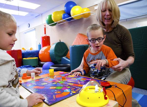 Occupational therapist Linda Merry, aids Michael Humphrey, 5, right, and his twin brother Nathan, 5, as they play the board game Splat! at the Easter Seals facility in Villa Park.