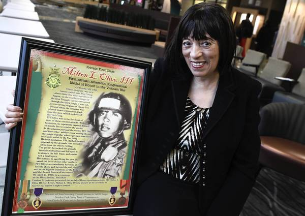 Chinta Strausberg, with a poster commemorating her cousin Milton Lee Olive III at Olive-Harvey College, is writing a book about her heroic cousin.