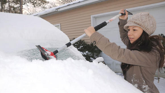 Andrea  Serveny brushes off her vehicle Tuesday morning after the overnight brought another fresh blanket of snow.