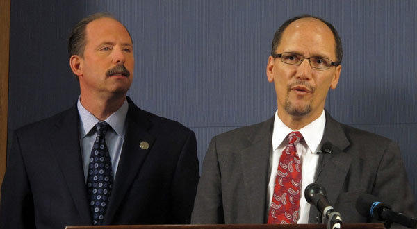 Thomas E. Perez, Assistant Attorney General for the Civil Rights Division is shown with Albuquerque Mayor Richard Berry, left, at a press conference in Albuquerque, N.M.