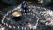 A man lights candles at the National AIDS Memorial Grove on December 1, 2011 in San Francisco, California.