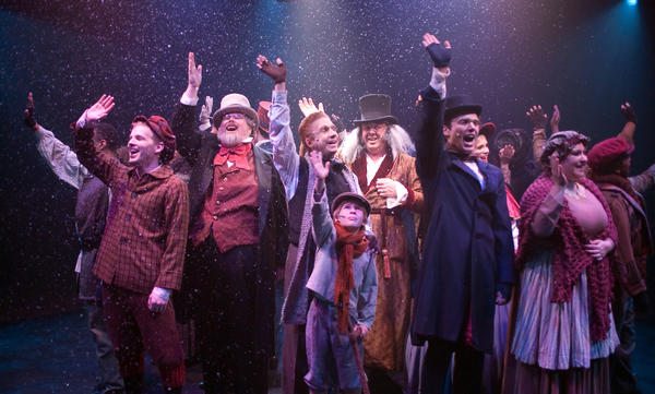 "The cast of Toby's Dinner Theatre's ""A Christmas Carol,"" including David Bosley-Reynolds, center, as Ebenzer Scrooge, waves."