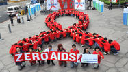 Dozens of volunteers join a human chain in the form of a red ribbon, a symbol of 'love and care' for HIV and AIDS carriers worldwide, at a gathering in downtown Taipei on November 30, 2011, ahead of World AIDS Day on December 1.