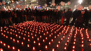 Participants prepare to release balloons while standing next to a sea of candles at the conclusion of a march to mourn the victims of AIDS on November 30, 2011 in Berlin, Germany.