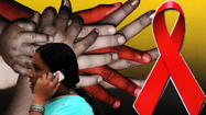 An Indian pedestrian speaks on a cellular telephone as she walks past a placard featuring details of an AIDS awareness programme on World AIDS day in Bangalore on December 1, 2010.