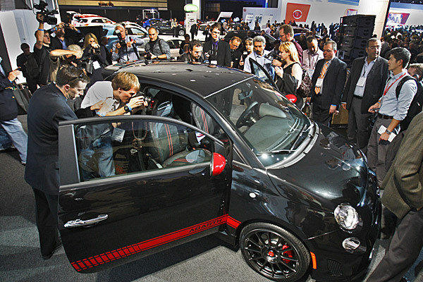 Journalists gather around a Fiat 500 Abarth at the 2011 L.A. Auto Show. The 2012 show opens to the public Friday and runs through Dec. 9.