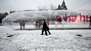 A Japanese couple walk past a giant 25-meter long condom as people gather inside it during an AIDS awareness event marking World AIDS Day in Budapest on December 1, 2010.