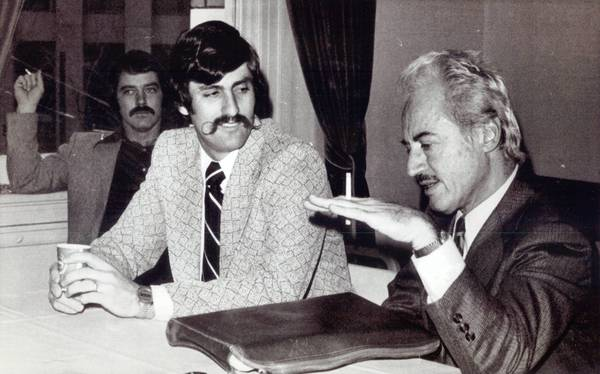 Marvin Miller, right, head of the Major League Players Association, chats with pitcher Rollie Fingers, center, as Fingers and pitcher Darold Knowles, left background, wait for the start of an arbitration session Oakland A's owner Charles Finley on Feb. 12, 1974 in San Francisco.