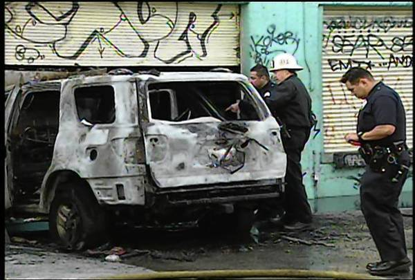 The SUV in which two children were burned to death is examined in the garment district of downtown Los Angeles.