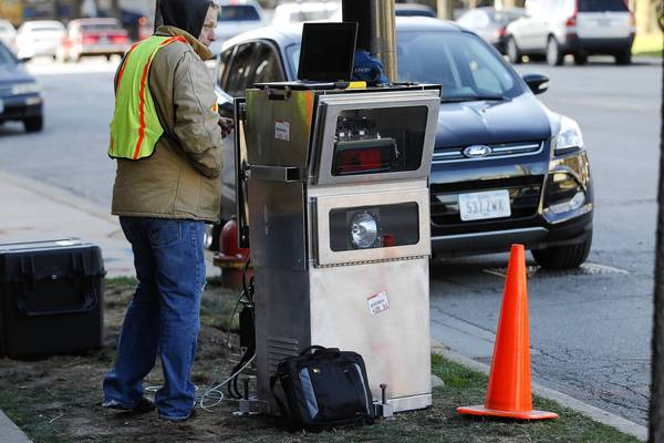 Workers who did not want to identify themselves or the company they were working for install a device Tuesday near 2323 W. Pershing Road in Chicago. The city has said a speed camera will be tested in that area.