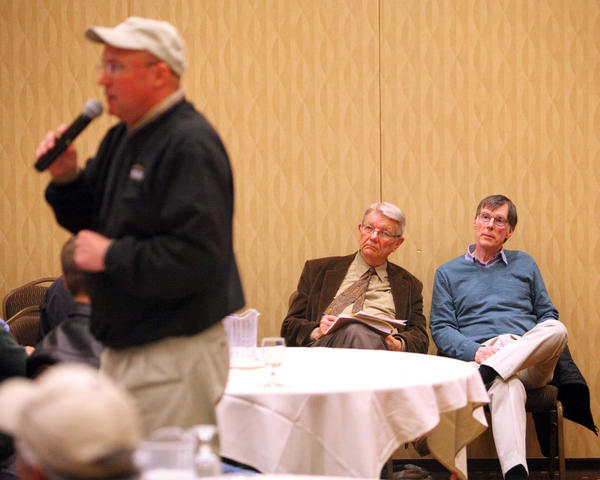 Attorney Carlyle Richards, center and Art Russo, right, one of the land owners selling Tuesday, right, look on as Jim Thorpe, of Thorpe Realty and Auction conducts the land auction at the Dakota Events Center. American News Photo by John Davis