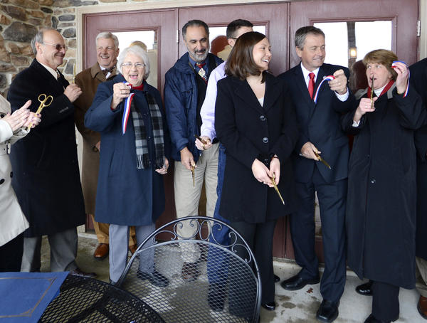 From left, Washington County Commissioners William McKinley and John Barr, Edna Naylor, Joe Fiola, winery owners Kevin and Yvonne Ford, County Commissioner Terry Baker and Liz Jones give a cheer after cutting the ribbon at the ceremony Tuesday celebrating the opening of Red Heifer Winery.
