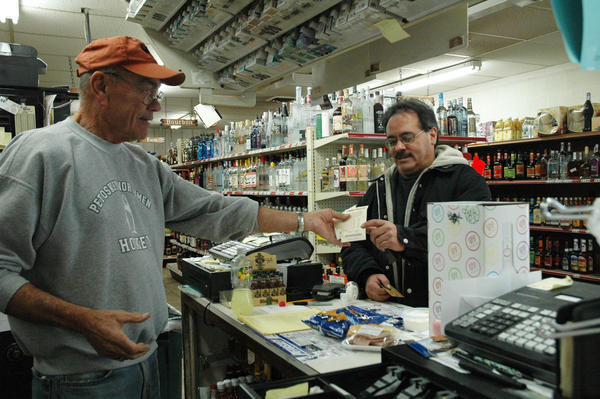 Bill Hansen Sr. hands Powerball tickets to customer Michael Hernandez of Petoskey on Tuesday at Bill and Carol's West Side Grocery in Petoskey. The Powerball Lottery drawing  for a pot of $500 million  will take place today, Wednesday.