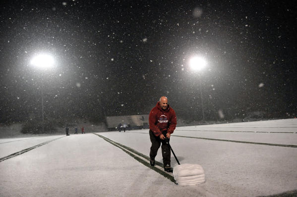 BERLIN 11/27/12 Dan Scavone, of Hamden, helps shovel snow off the yard lines at Sage Park in Berlin in preparation for the Class M quarterfinal football game between Berlin and Bullards Haven Tech Tuesday night. Scazone is the Berlin High School athletic director