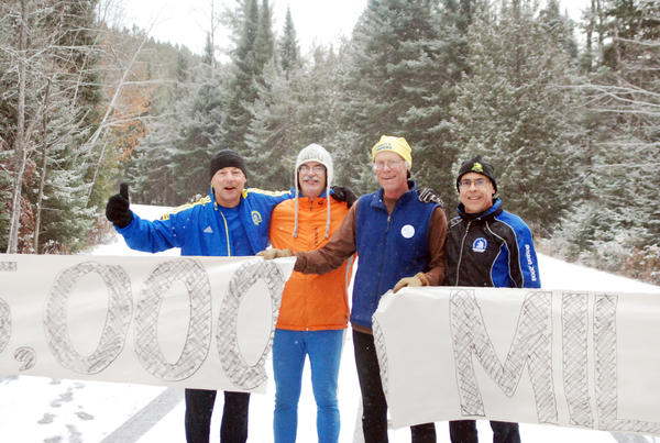 Ellis Boal (second from right) of Charlevoix celebrates his 75,000th career lifetime mile of running Sunday at Young State Park in Boyne City with running partners and friends (from left) Robert Grove, Hap Wright and Alan McCutcheon.