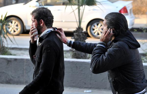 Two injured Syrian men near the scene of a car bomb explosion in Jaramana, a mainly Christian and Druze suburb of Damascus.