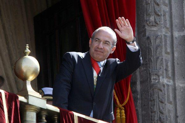 Mexican President Felipe Calderon waves from the presidential palace. He hands over his post Saturday to Enrique Pea Nieto.