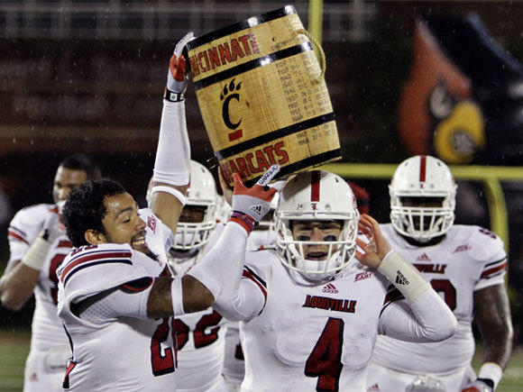 "Louisville players -- led by Jordon Paschal (22) and Will Stein (4) -- celebrate with the ""Keg of Nails"" trophy after beating Cincinnati in overtime this year."