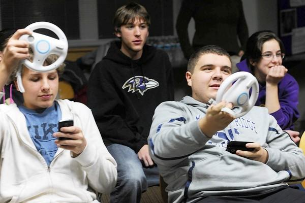 Marriotts Ridge High School  juniors Trevor Flach, left, and Mikel Bentivenga try to operate a Wii steering wheel while playing Mario Kart and texting simultaneously during a distracted driving workshop put on by the Voices for Change  Tuesday, Nov. 27 at the Glenwood Branch Library.