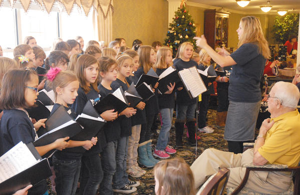 The Petoskey Elementary enrichment choir, under the direction of Stephanie Asiala-Gross (left), performs holiday songs for an audience at Independence Village in Petoskey, Tuesday. The enrichment choir performed six times Tuesday at Petoskey elementary schools, Independence Village, and finished the day with a free public concert at the Petoskey High School auditorium, Tuesday evening. The choir is made up of elementary students from all Petoskey elementary schools and entertain throughout the year.