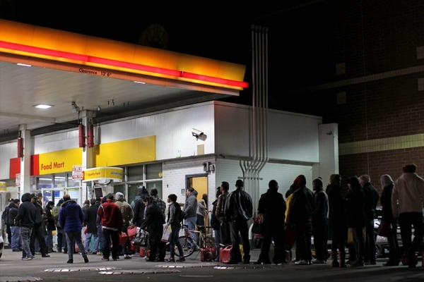Police organize a line of New Yorkers hoping to buy fuel after Hurricane Sandy shut down some refineries in the region. Americans will spend a record $483 billion on gasoline in 2012, the Oil Price Information Service says.