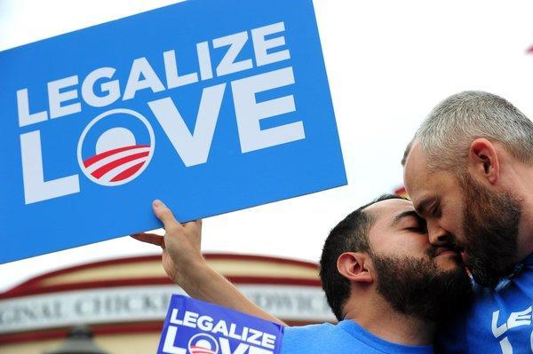 "Demonstrators Eduardo Cisneros, left, and Luke Montgomery kiss. An AP rule on use of the term ""homophobia"" has set off a spirited debate among journalists."