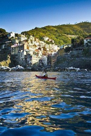 A sea kayaker approaches Riomaggiore, one of villages in Italy's Cinque Terre section.