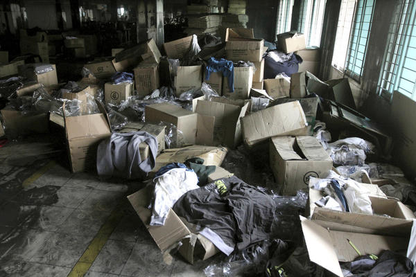 Boxes of garments lay near equipment charred in the fire that killed 112 workers Saturday at the Tazreen Fashions Ltd. factory,on the outskirts of Dhaha, Bangladesh, Wednesday. Garments and documents left behind in the factory show it was used by a host of major American and European retailers, though at least one of them - Wal-Mart - had been aware of safety problems. Wal-Mart blames a supplier for using Tazreen Fashions without its knowledge.